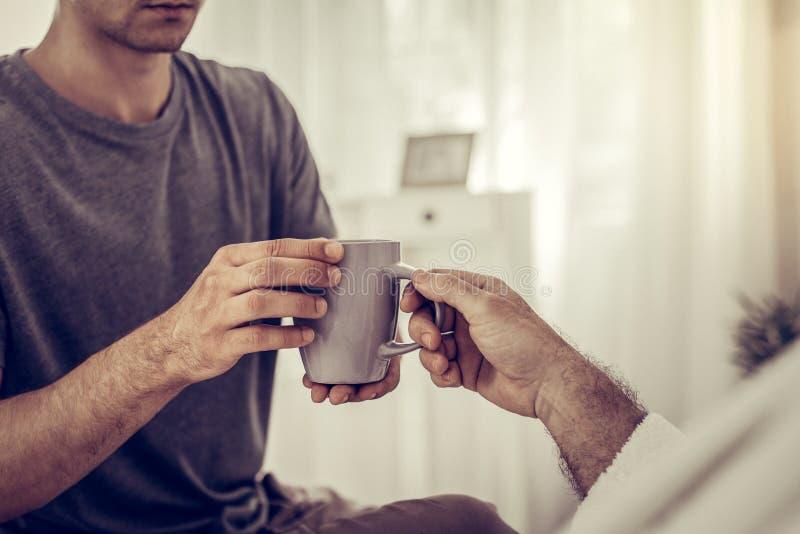 Фото конца-вверх человека вручая чашку к больному человеку стоковые фото