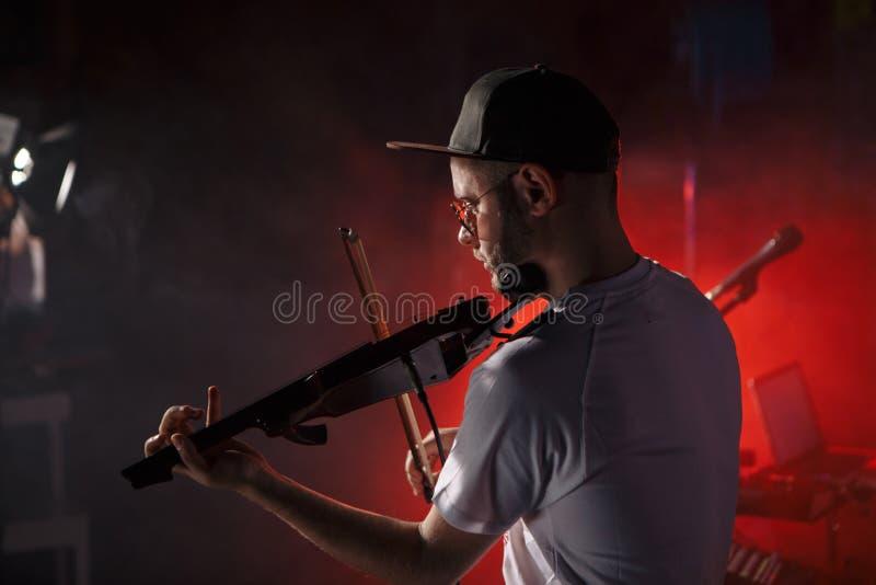 Фото конца-вверх человека играя электрическую скрипку стоковые фотографии rf