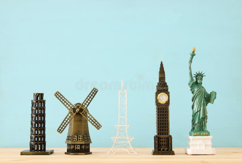 фото концепции некоторого из ориентира для перемещения, небольших статуй мира известного над деревянным столом стоковое изображение