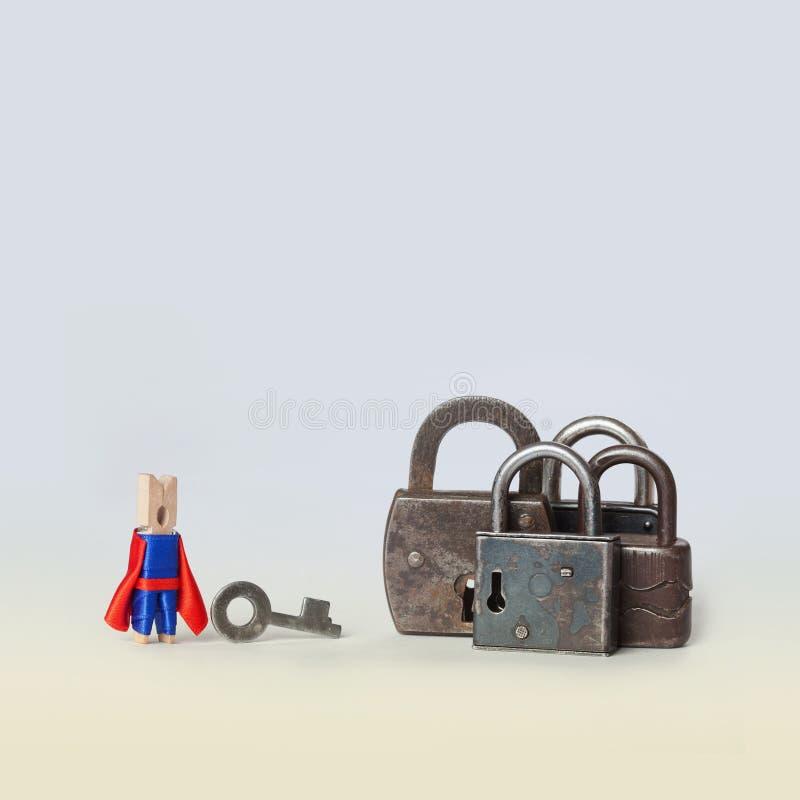 Фото концепции отверстия locked padlock Характер консервооткрывателя супергероя в голубом, красном костюме с ключом и металл фикс стоковые фотографии rf