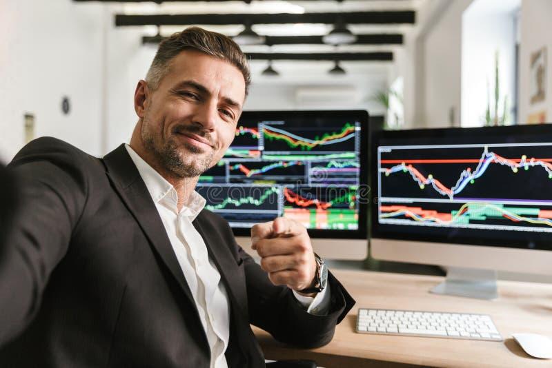 Фото красивого человека принимая selfie пока работающ в офисе на компьютере с графиками и диаграммами на экране стоковое фото