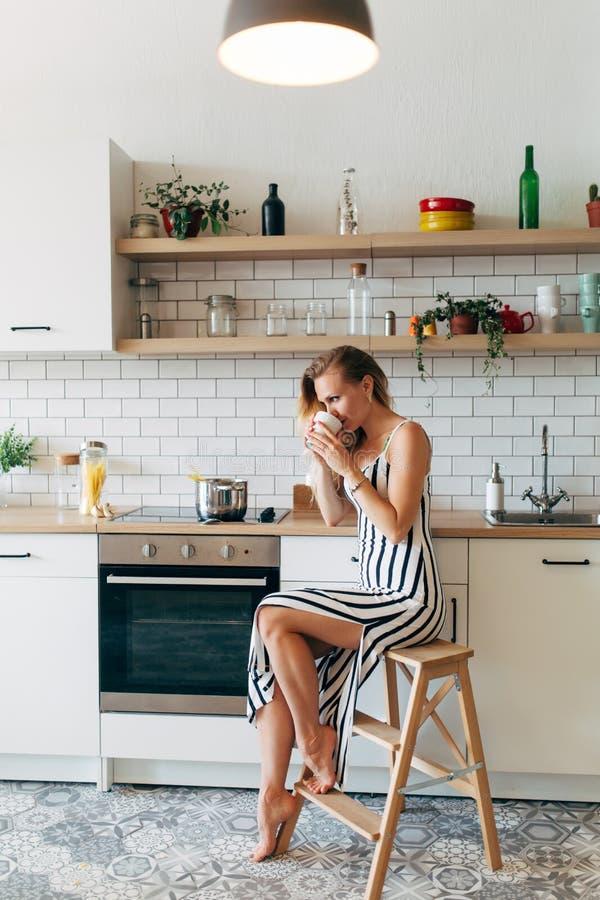 Фото красивой женщины в длиной striped платье в кухне стоковые фотографии rf