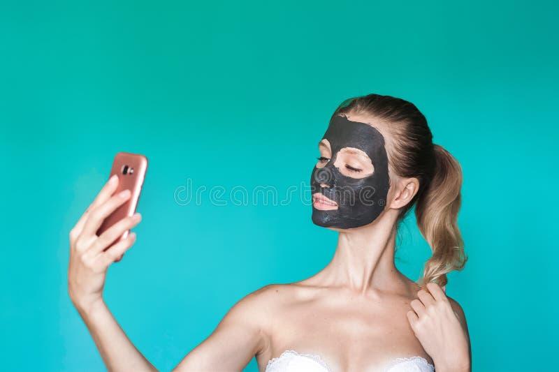 Фото красоты женщины с черной маской на ее стороне держит телефон в ее руках и делает selfie на предпосылке голубого turq стоковое изображение rf