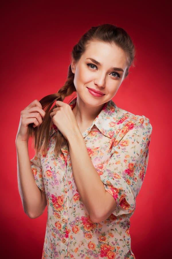 Фото красоты кавказской модели на красной предпосылке стоковое изображение