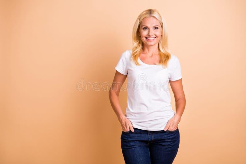 Фото крупного плана бежа джинсов футболки носки возникновения дамы среднего возраста усмехаясь ясной белой случайной изолированно стоковая фотография rf