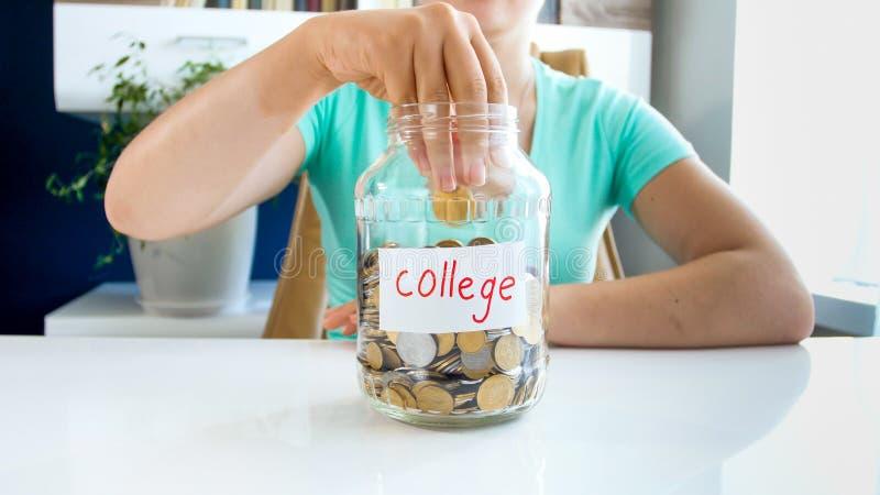 Фото крупного плана денег молодой женщины бросая в стеклянном опарнике с сбережениями для образования в коллеже стоковые фотографии rf