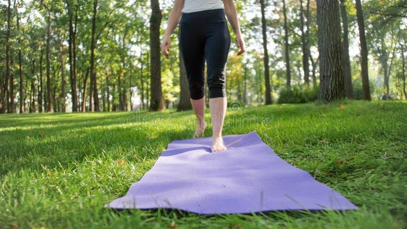 Фото крупного плана женских ног идя на циновку фитнеса лежа на траве на парке Женщина делая тренировки йоги в природе стоковое изображение rf