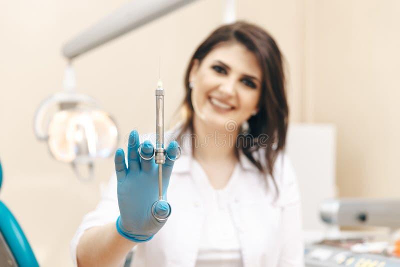 Фото крупного плана женского дантиста в зубоврачебной комнате держа устный шприц стоковое изображение