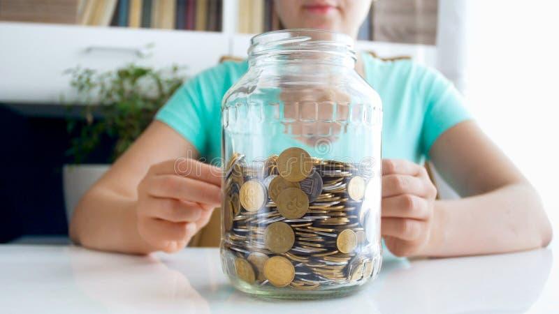 Фото крупного плана женщины oyung сидя за столом и смотря на стеклянном опарнике вполне монеток стоковые фотографии rf