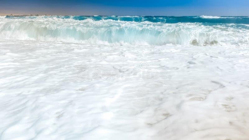 Фото крупного плана красивых волн моря ломая на береге Влажные песок и вода брызгают на пляже стоковое изображение rf