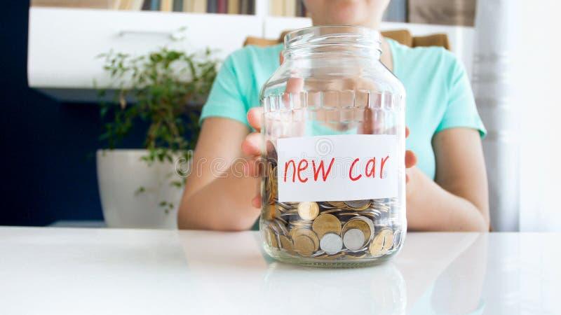 Фото крупного плана молодой женщины держа стеклянный опарник полный денег для покупать новый автомобиль стоковое изображение