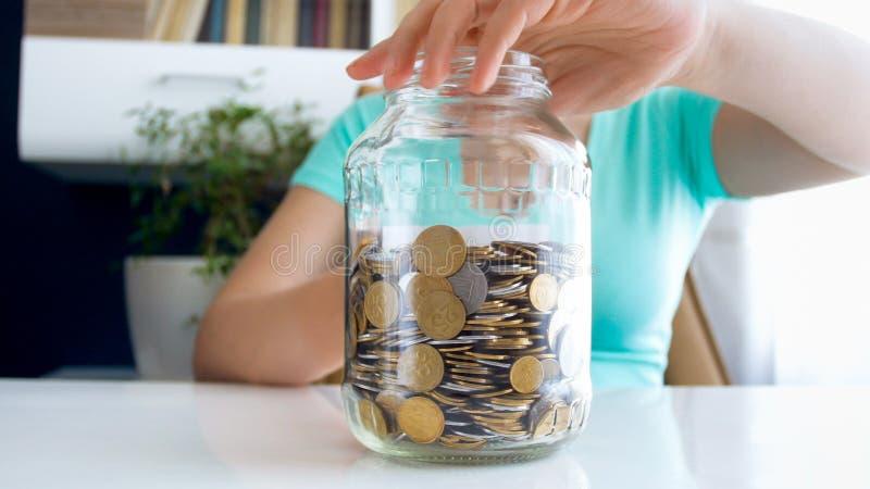 Фото крупного плана молодой женщины держа стеклянный опарник полный монеток стоковая фотография rf