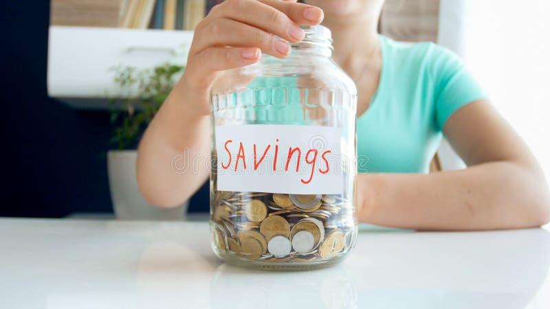 Фото крупного плана молодой женщины сидя за столом и держа стеклянный опарник с сбережениями денег стоковые фотографии rf