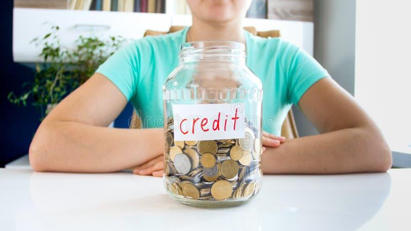 Фото крупного плана молодой женщины с стеклянным опарником полным монеток и обозначенного кредита стоковая фотография rf