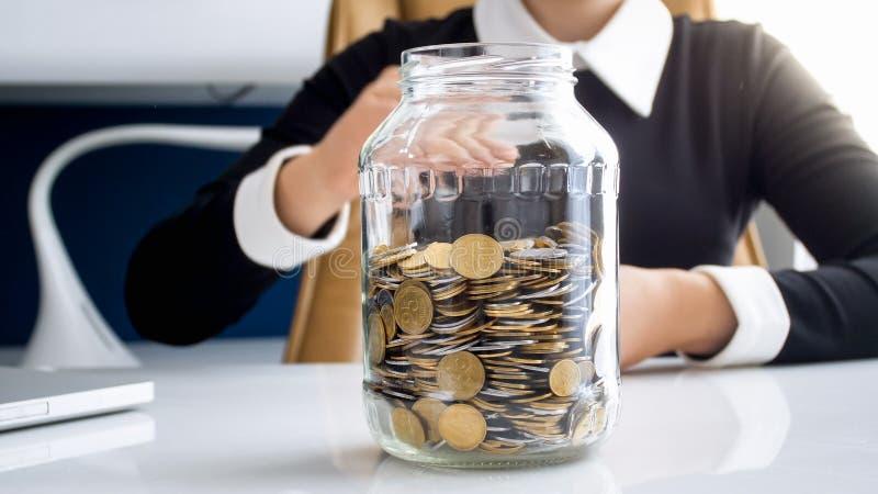 Фото крупного плана молодой коммерсантки на офисе с стеклянным опарником полным монеток стоковые изображения