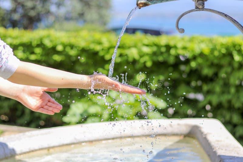 Фото крупного плана рук маленькой девочки моя в фонтане города при вода брызгая на их с много падениями стоковое изображение