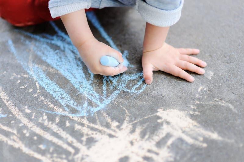 Фото крупного плана чертежа мальчика маленького ребенка с покрашенным мелом на асфальте стоковые изображения
