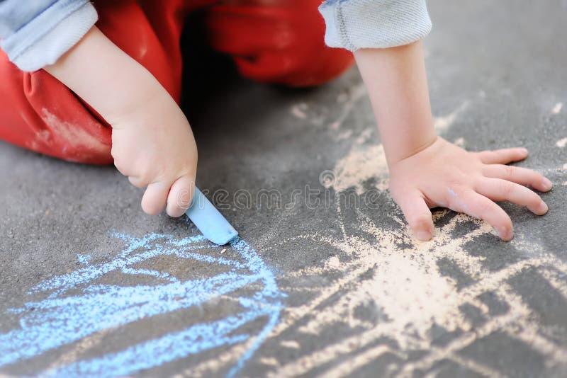 Фото крупного плана чертежа мальчика маленького ребенка с покрашенным мелом на асфальте стоковая фотография rf