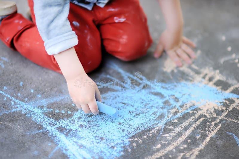 Фото крупного плана чертежа мальчика маленького ребенка с покрашенным мелом на асфальте стоковая фотография