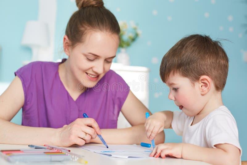 Фото ласковой матери рисует изображение к ее маленькому сыну, тратит ime совместно дома, имеет положительные улыбки, дружелюбные  стоковые изображения rf