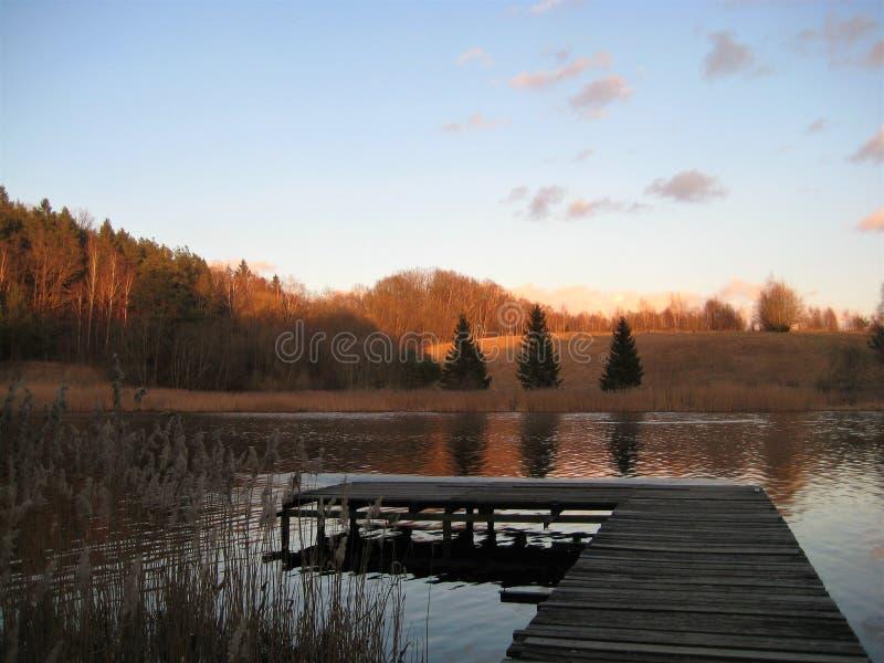 Фото макроса с предпосылкой сельского ландшафта декоративной выравнивать заход солнца в предыдущей весне на озере в Литве стоковое фото rf