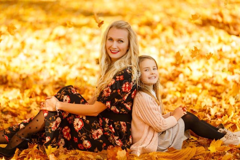 Фото матери и дочери сидя на листьях в осени стоковые изображения