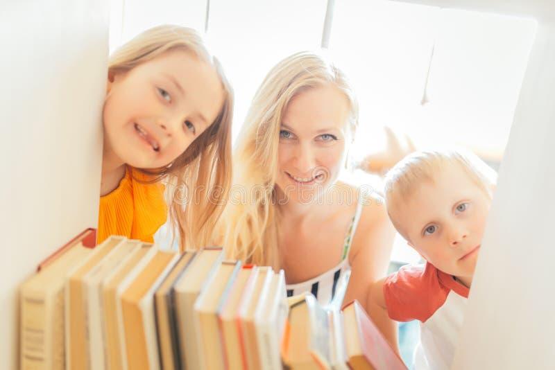 Фото матери при сын и дочь смотря прищурясь из укрытия с книгами стоковые фотографии rf