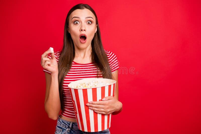 Фото модной брюнетки, испуганной девушки, едящей попкорн в полосатой футболке, смотрящей фильм ужасов стоковые фотографии rf