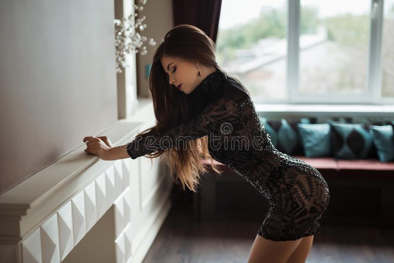 Фото моды красивой дамы одело в выравнивать черное платье шнурка Молодая женщина представляя в чувственном пути внутри помещения стоковые изображения