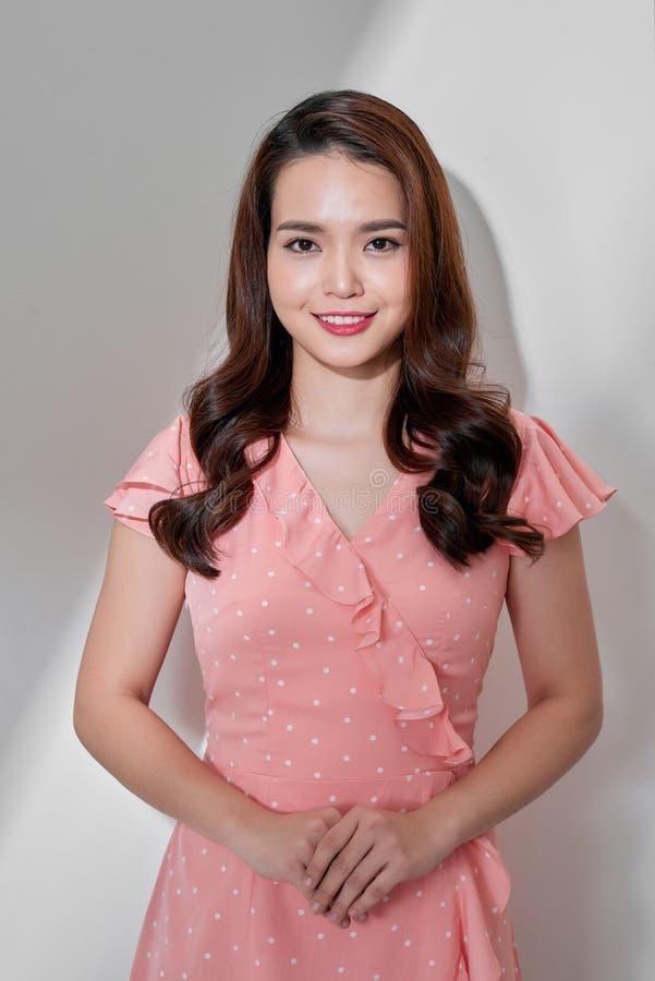 Фото моды красивой молодой женщины в милом платье с точкой польки представляя над серой предпосылкой r стоковые фото