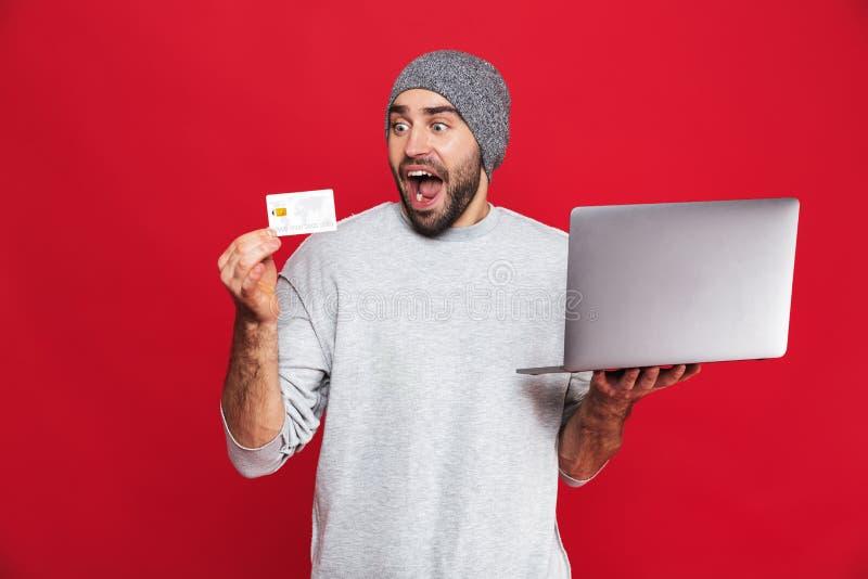 Фото молодого парня держа кредитную карточку и серебряный ноутбук изо стоковые фото