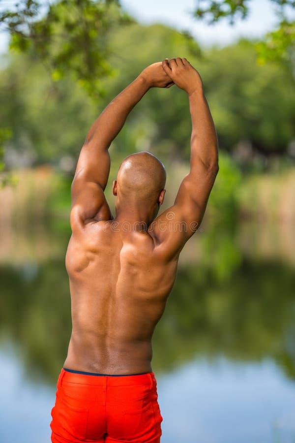 Фото молодой Афро-американской модели фитнеса протягивая в парке Человек представляя без рубашки показывая мышцы стоковые изображения rf