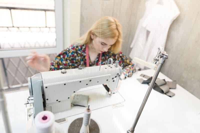 Фото молодой белошвейки на швейной машине Работа Dressmaker на швейной машине стоковое фото rf