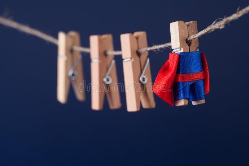 Фото мощного супергероя схематическое с характером зажимки для белья суперзвезды в голубой накидке красного цвета костюма руковод стоковые изображения rf