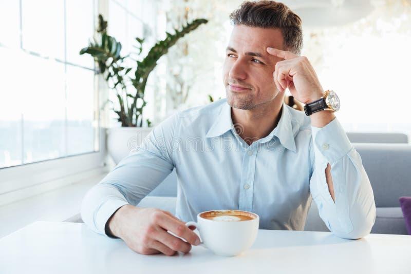 Фото мужеского человека 30s сидя самостоятельно в кафе города с чашкой o стоковое изображение rf