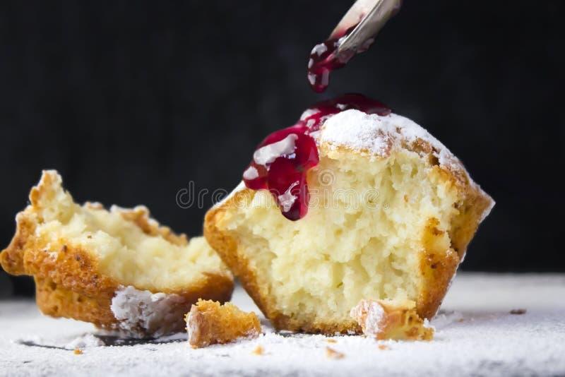 Фото напудренное при булочка сахара сломанная в 2 частях Чайная ложка и красное варенье Селективный мягкий фокус, место для текст стоковые фото