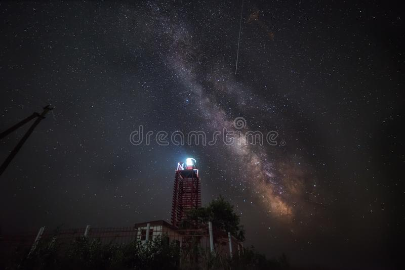 Фото ночи Млечный путь и падающие звезды метеорного потока Perseid в августе над прибрежным маяком стоковые изображения rf