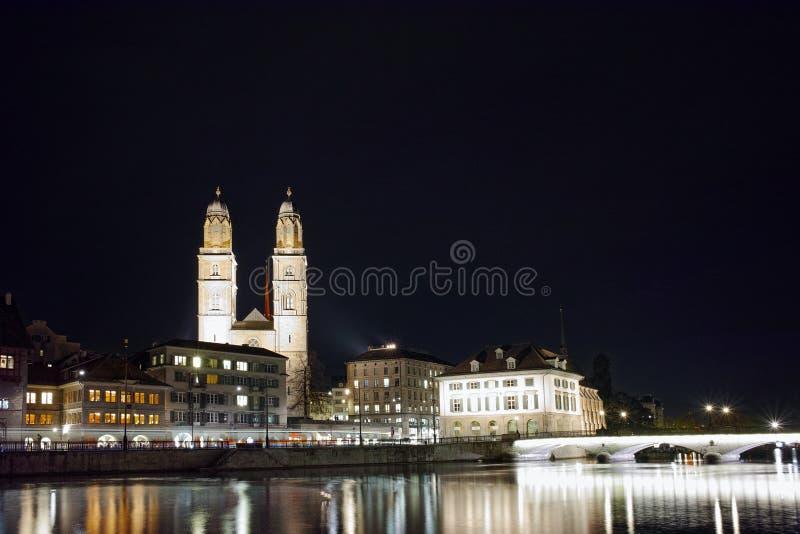 Фото ночи церков Grossmunster и мост над рекой Limmat, Цюрихом, Швейцарией стоковая фотография