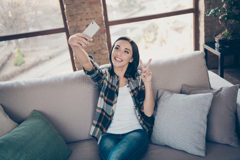 Фото очаровательной леди, держащей телефон, делает селфи для блога, показывая символ v-sign, сидящий комфортабельно на диване стоковая фотография rf