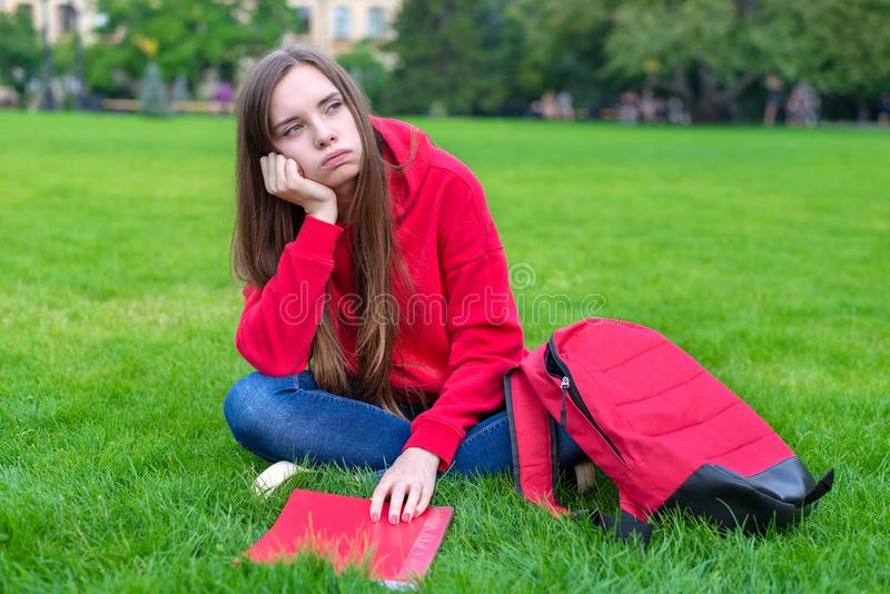 Фото подавленной пассивной грустной предназначенной для подростков девушки сидя на лужайке зеленой травы не охотно готово сделать стоковые изображения