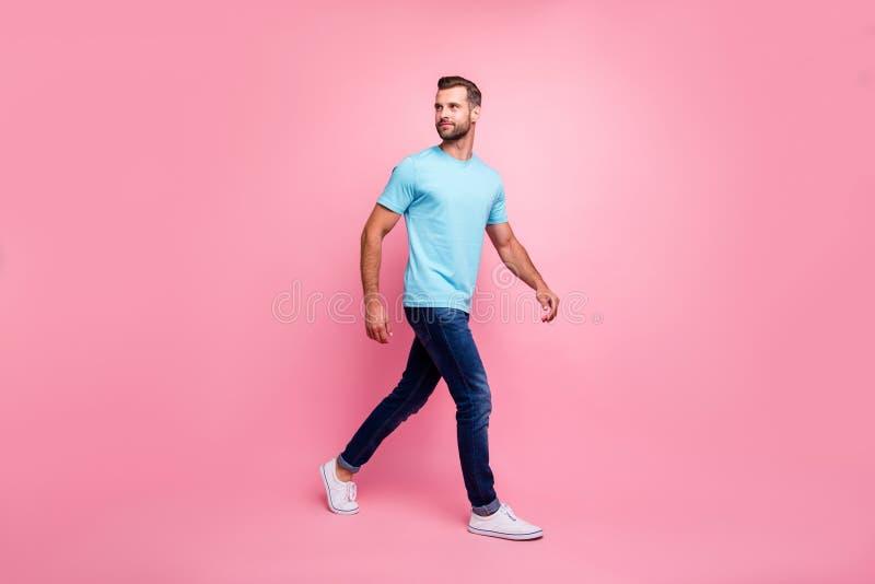 Фото превращенного человека в джинсах denim, идущего вперед, оглядываясь назад в кроссовках, изолированных пастельных цветов фона стоковое изображение rf