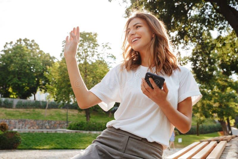 Фото приветливой дружелюбной женщины сидя на стенде в зеленом парке o стоковое изображение