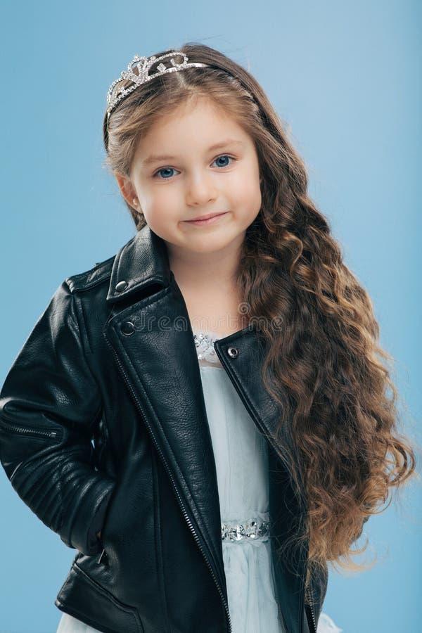 Фото привлекательной женщины с вьющиеся волосы, имеет одетые голубые глазы, в кожаной черной куртке, держит руки в карманах, моде стоковая фотография rf