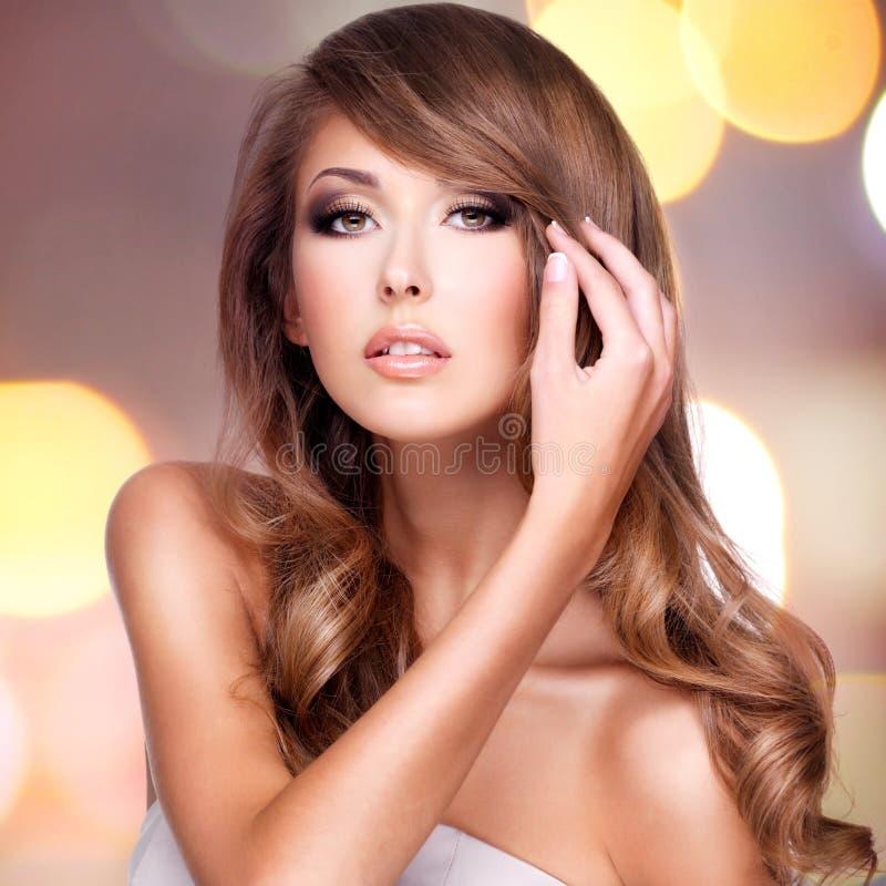 Фото привлекательной женщины касаясь ее красивым волосам стоковая фотография rf