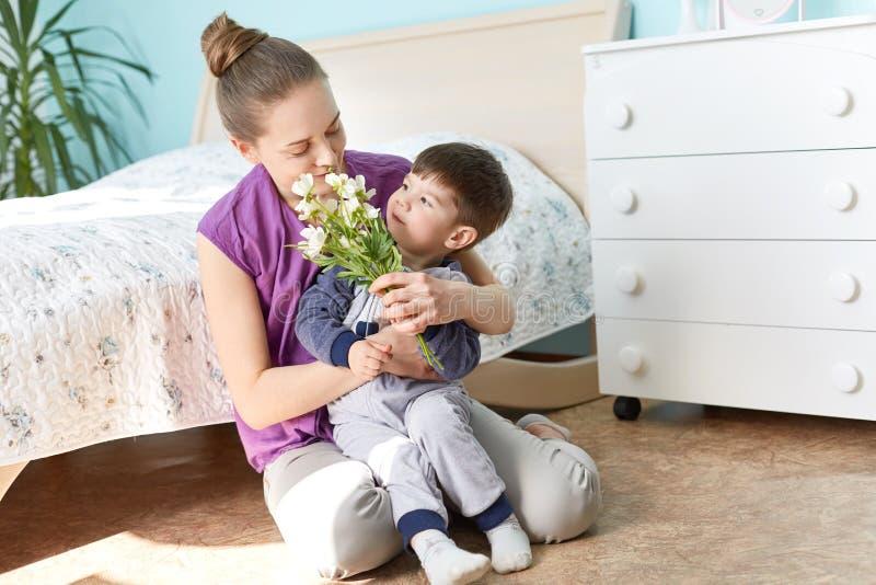 Фото приятной смотря молодой женщины держит ее малого милого сына на руках, игры совместно в спальне, сидит на поле около кровати стоковая фотография rf