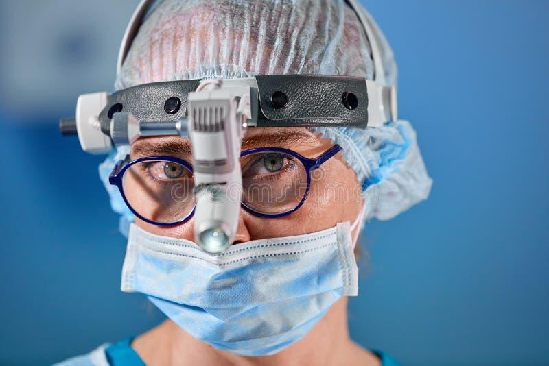 Фото работая хирурга в комнате хирургии Хирург в маске и стекла с установленной фарой Близкий портрет стоковые изображения