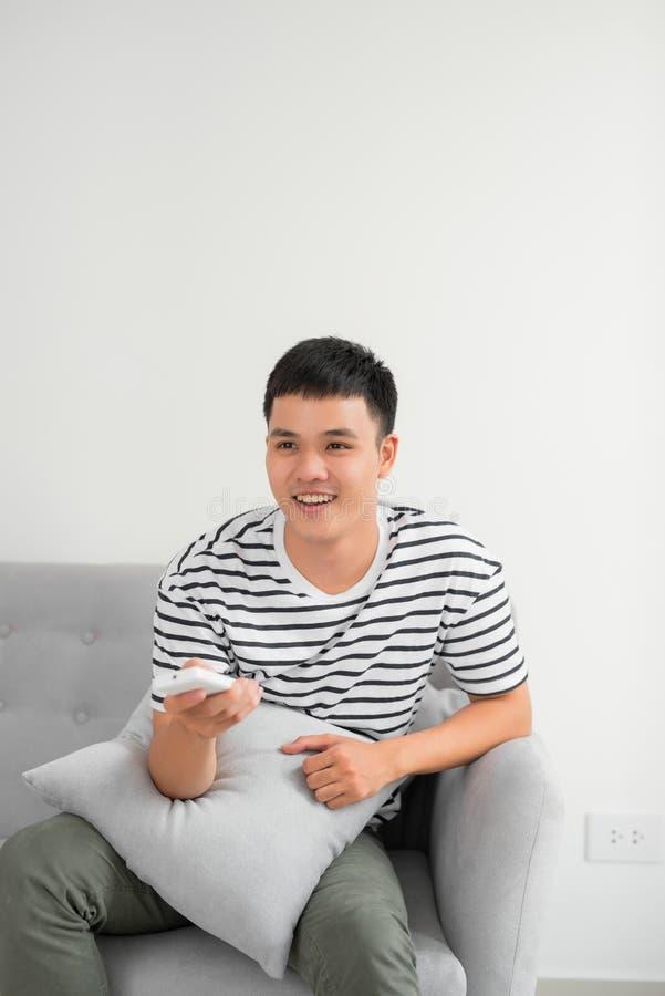 Фото радостного человека 30s в случайной одежде сидя на софе в живя комнате и смотря на камере с дистанционным управлением в руке стоковые изображения