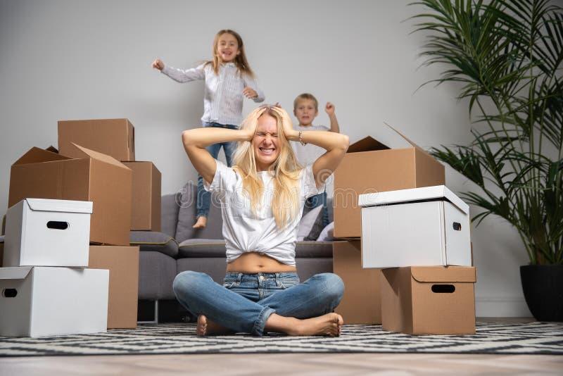 Фото раздражанной женщины сидя на поле среди картонных коробок и мальчика, девушки скача на софу стоковые фотографии rf