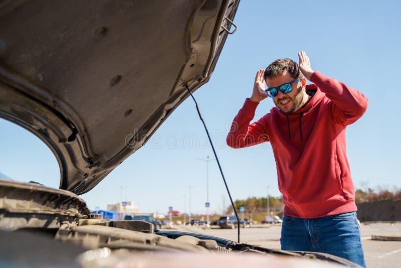 Фото расстроенного человека с руками за головой рядом с открытым клобуком сломленного автомобиля в дневном времени стоковые фотографии rf