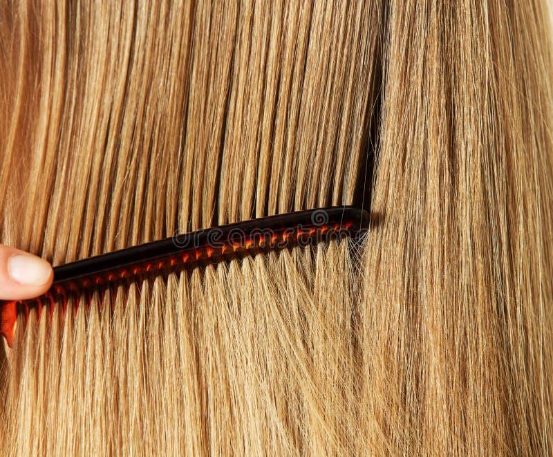 Фото расчесывать женщину с длинными светлыми волосами стоковые изображения rf